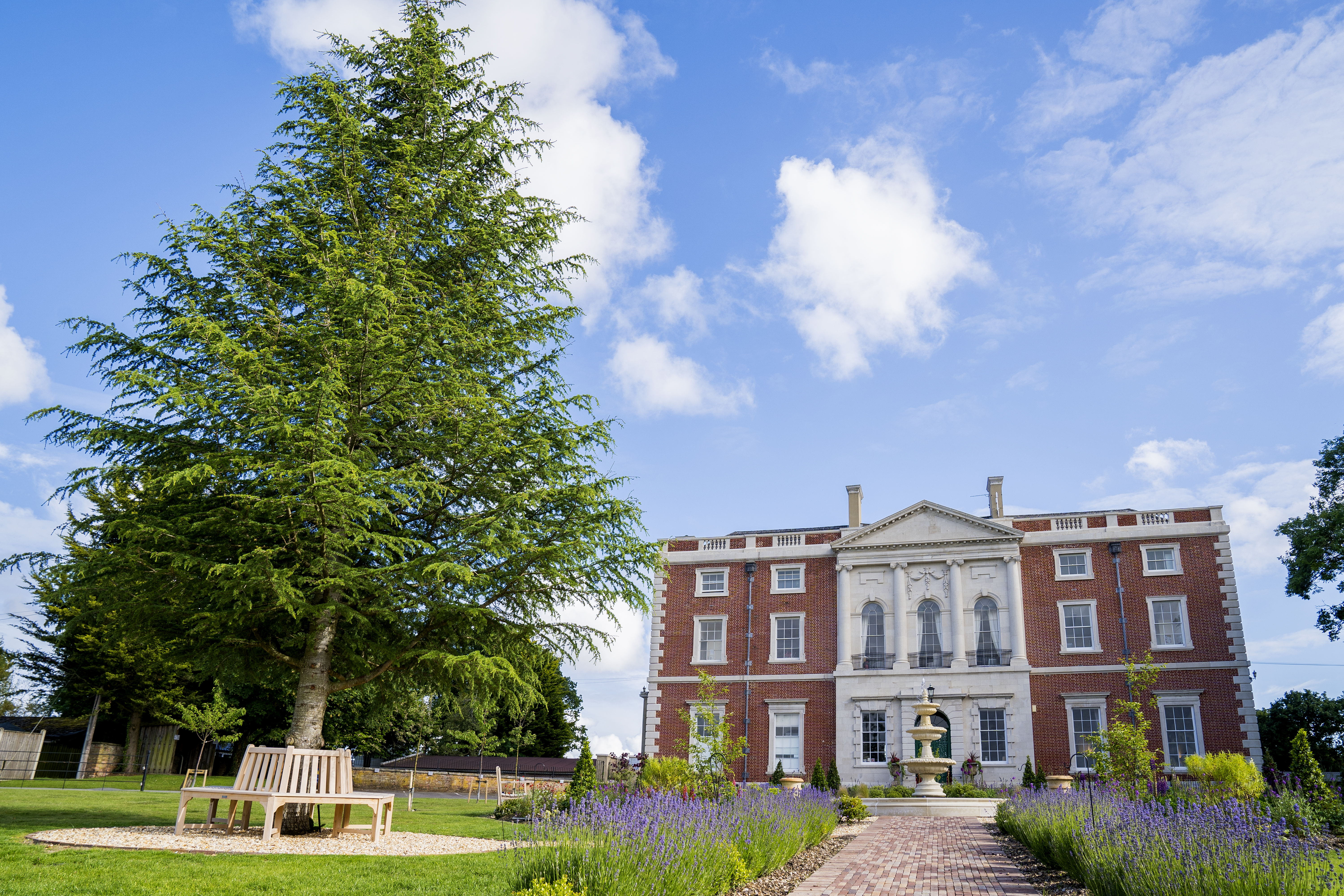 A grand 18th century manor house situated behind a garden with a fountain