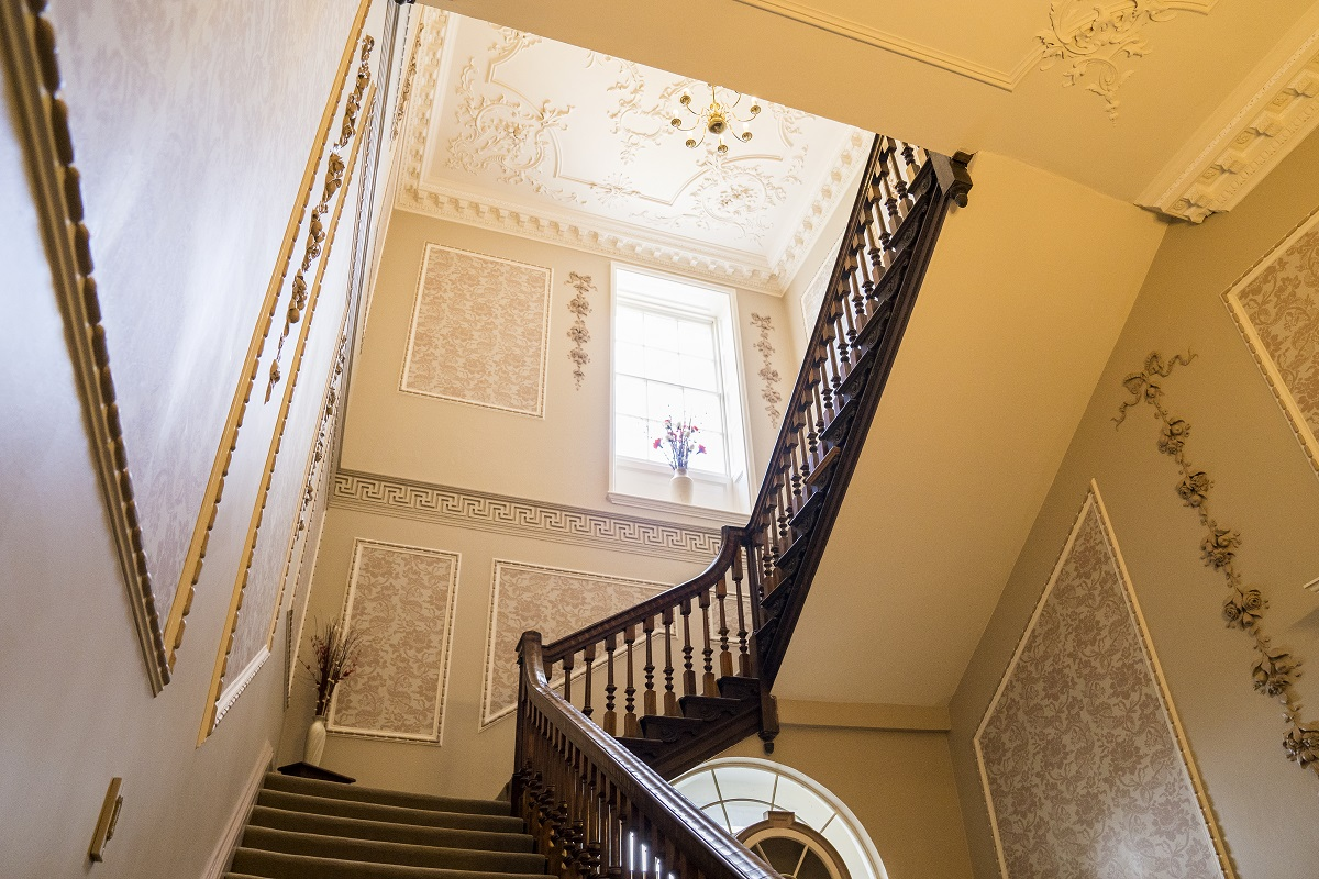 an ornate staircase with wooden railings and carpeted floors