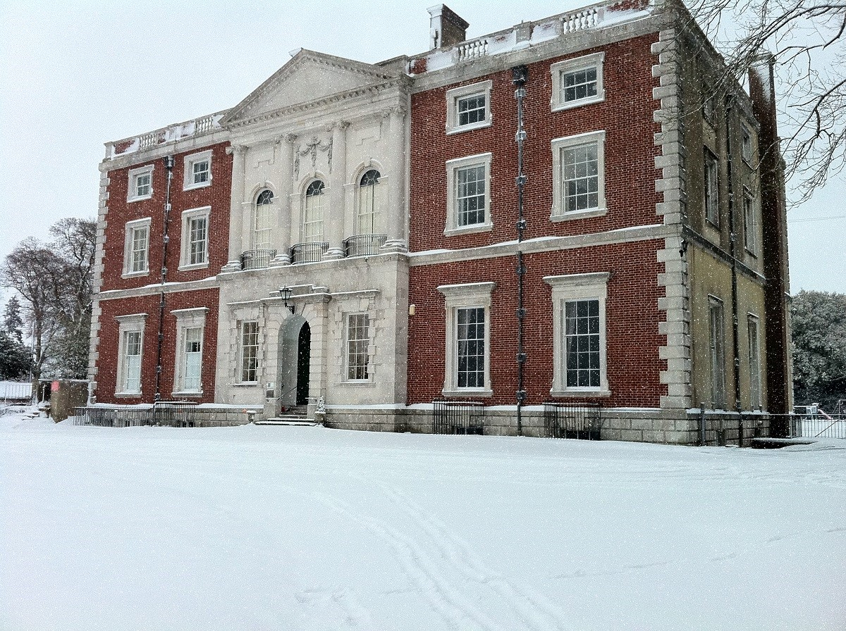 a grand Georgian manor house surrounded by snow